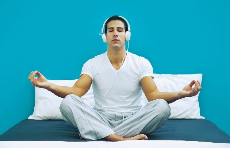 meditation with earphones on bed