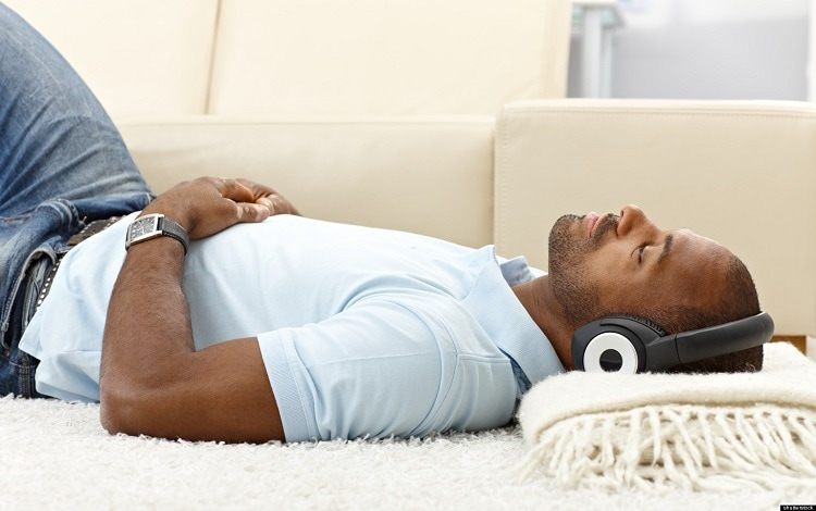 man lying on couch with headphones