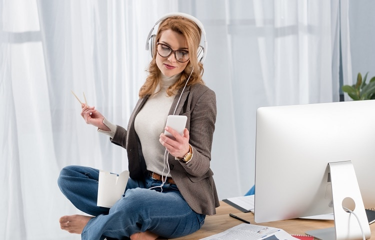 businesswoman listening music on table in office