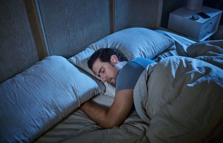 man sleeps with earbuds